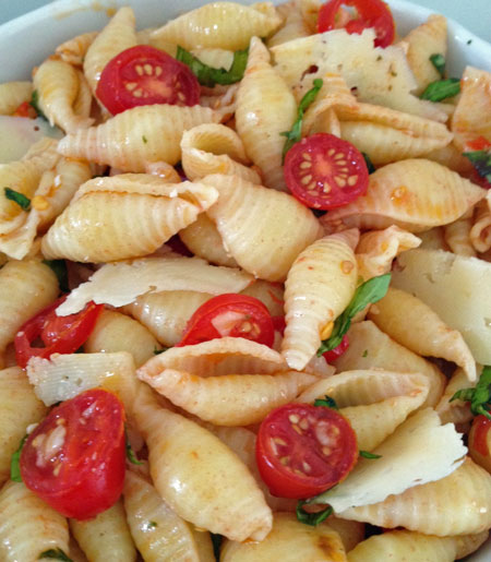 Seashell pasta salad with basil, tomatoes, and garlic